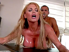 Taylor Wane leans against a desk to get her vag fucked from behind