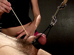 Skinny dominatrix with long dark hair torturing a stranger