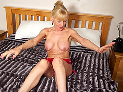Mature blonde MILF Elaine strips and masturbates in high heels